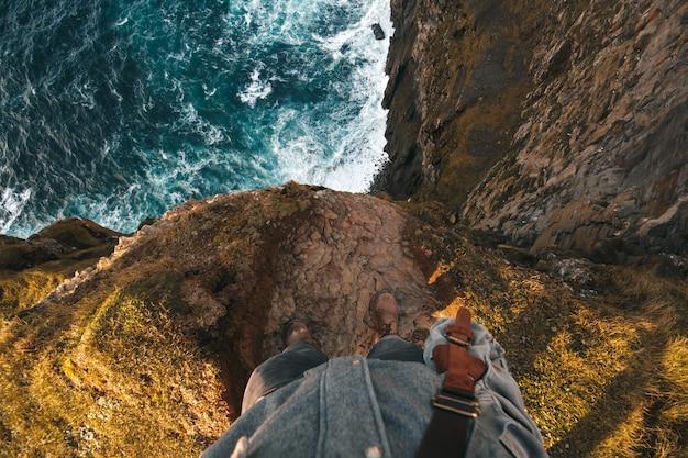 절벽의 가장자리에 서있는 사람의 꼭대기에서 관점