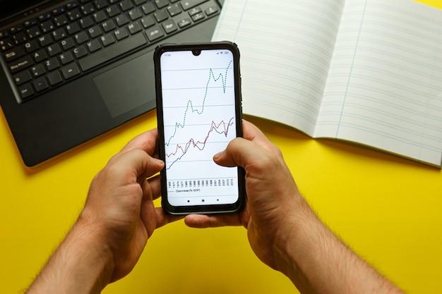 経済的なグラフィックを備えた電話をつかむ2つの若い手の視点