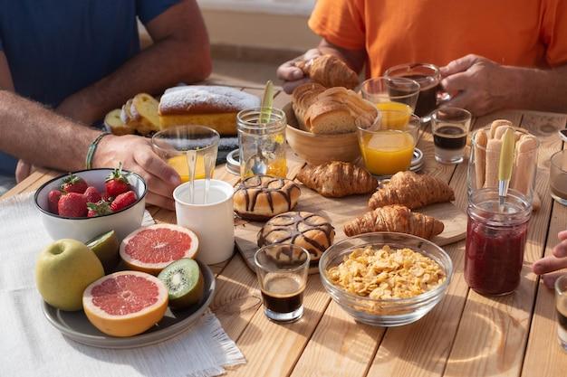 朝食用に設定された木製のテーブルの視点。太陽の下のテラスのテーブル。新鮮な果物と甘い食べ物で一日をスタート、3人家族