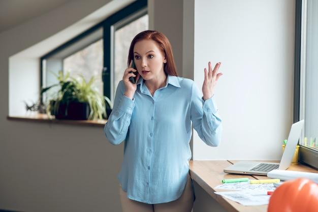 Точка зрения. молодая взрослая красивая уверенная в себе женщина общается с помощью смартфона, жестикулируя рукой, стоящей возле чертежей и ноутбука на подоконнике
