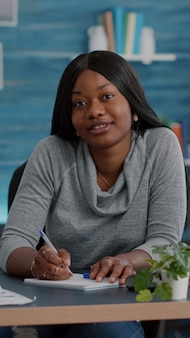Point of view of student with dark skin smiling at camera during communication videocall telework conference meeting. african american woman sitting at desk in living room working remote from home