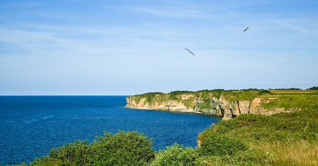 Скалы пуэнт-дю-хок в чистом небе и спокойном море.