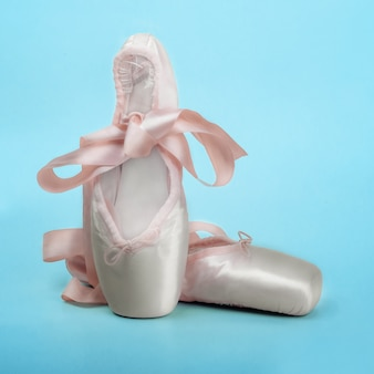 Pointe shoes ballet dance shoes with a bow of ribbons beautifully folded on blue