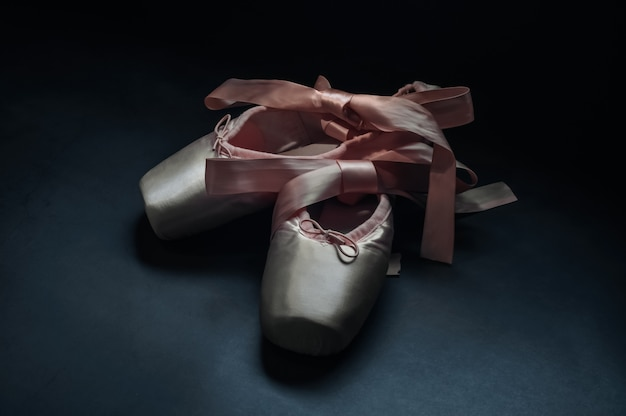 Pointe shoes ballet dance shoes with a bow of ribbons beautifully folded on a dark background.