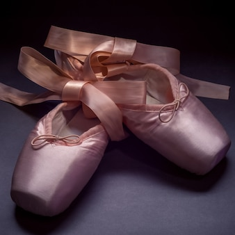 Pointe shoes ballet dance shoes with a bow of ribbons beautifully folded on dark