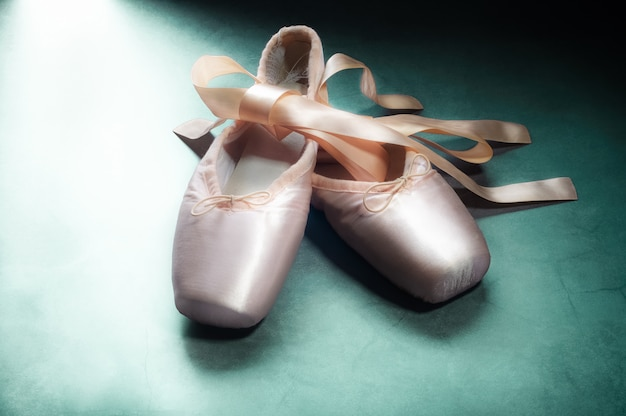 Pointe shoes ballet dance shoes with a bow of ribbons beautifully folded on green