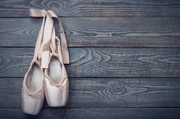 Pointe shoes ballet dance shoes with a bow of ribbons hang on a nail on wood