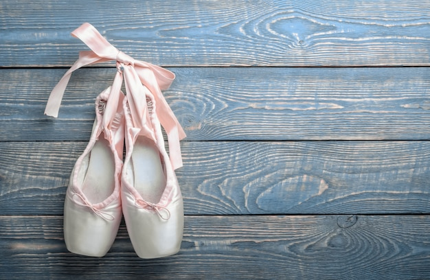 Pointe shoes ballet dance shoes with a bow of ribbons hang on a nail on a wooden background.
