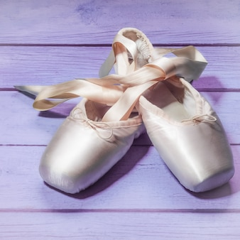 Pointe shoes ballet dance shoes with a bow of ribbons on a wooden background.