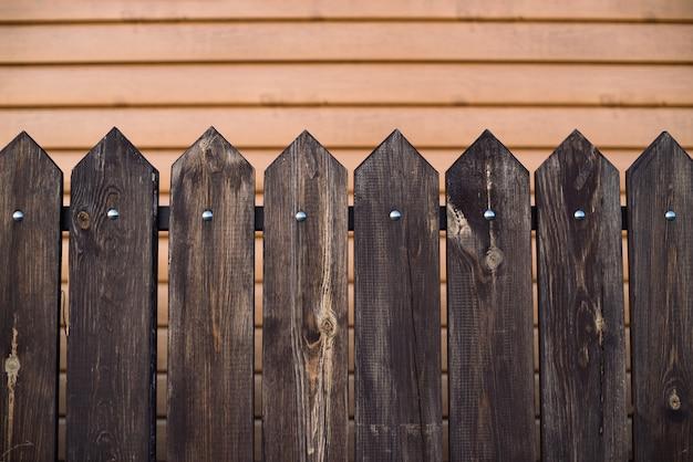 Заостренный деревянный забор на фоне дома с поверхностью от сайдинга. фоновое изображение деревянного забора из прямоугольных досок с треугольной вершиной. планки скреплены перекладиной и гвоздями.
