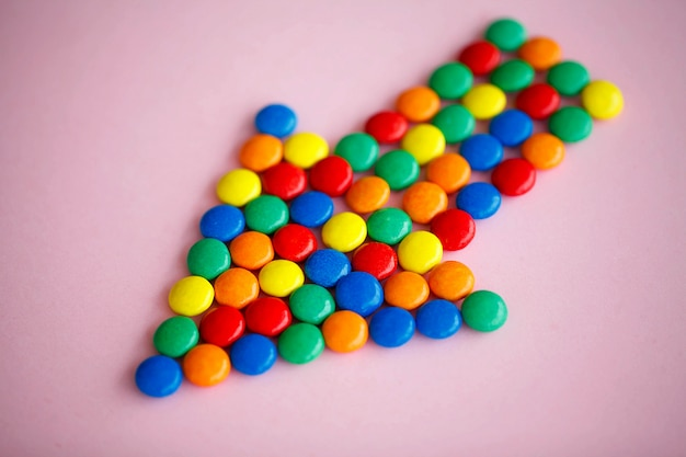 Pointer on the pink background, colored candy