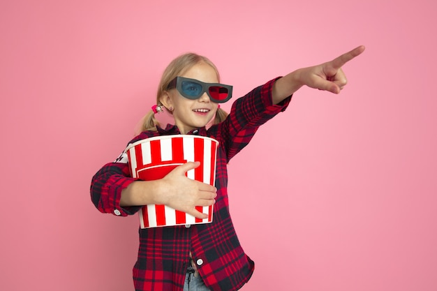 Pointing in 3d eyewear. caucasian little girl's portrait on pink wall. beautiful female model with blonde hair. concept of human emotions, facial expression, sales, ad, cinema, childhood.