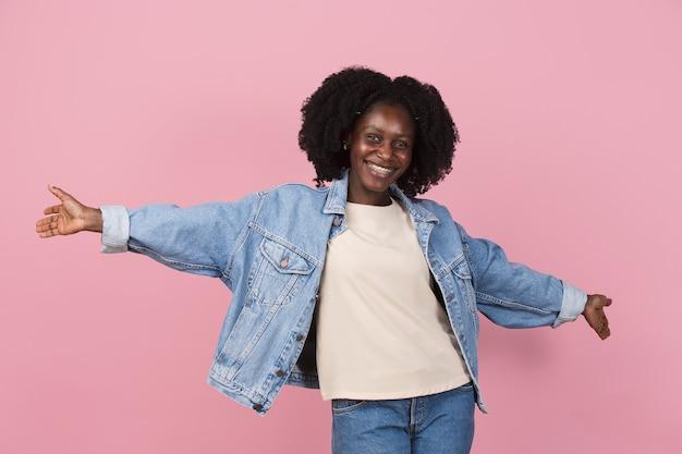 ポインティング。コピースペースとピンクの壁に分離されたアフリカ系アメリカ人の美しい女性の肖像画。スタイリッシュな女性モデル。人間の感情、顔の表情、、ファッション、若者の概念。 Premium写真