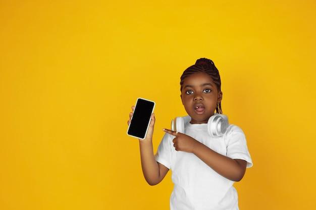전화를 가리키며 음악을 듣습니다. 노란색 스튜디오 배경에 있는 작은 아프리카계 미국인 소녀의 초상화. 쾌활한 아이. 인간의 감정, 표정, 판매, 광고의 개념. 카피스페이스. 귀여워 보인다.