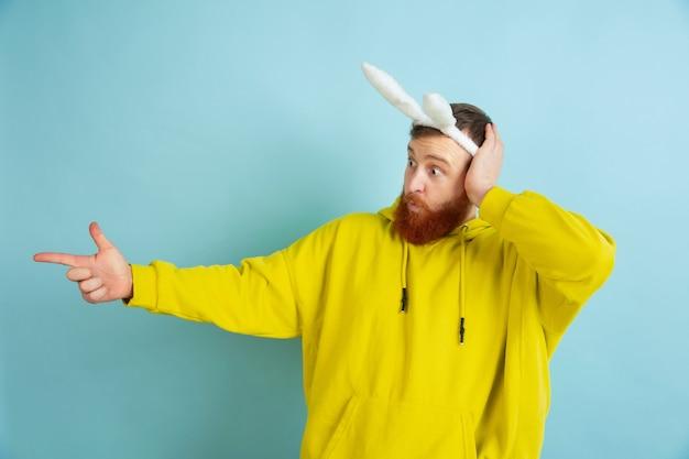 横を指しています。青いスタジオの背景に明るいカジュアルな服を着たイースターバニーとしての白人男性。