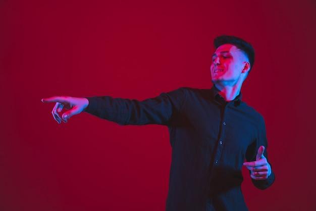 横を指しています。ネオンの光の中で赤い壁に分離された白人の若い男の肖像画。黒の美しい男性モデル。人間の感情、表情、若者文化の概念。