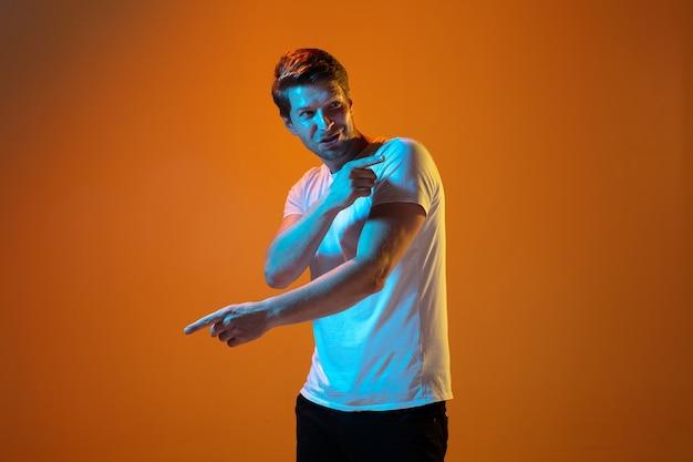 Указывая в сторону. портрет кавказского молодого человека на градиентном оранжевом фоне студии в неоновом свете. красивая мужская модель. понятие человеческих эмоций, выражения лица, продаж, рекламы. copyspace.