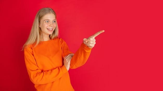 Указывая в сторону. портрет молодой кавказской женщины изолированной на красной предпосылке студии с copyspace. красивая женская модель. понятие человеческих эмоций, выражения лица, продаж, рекламы, молодежи. листовка