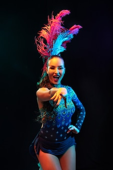Pointing. beautiful young woman in carnival, stylish masquerade costume with feathers on black wall in neon light. copyspace for ad. holidays celebration, dancing, fashion. festive time, party.