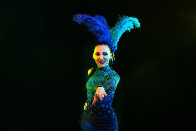 가리키는. 네온 불빛에 검은 바탕에 깃털을 가진 카니발, 세련 된 무도회 의상에서 아름 다운 젊은 여자. 광고 copyspace입니다. 휴일 축하, 춤, 패션. 축제 시간, 파티.