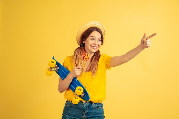 가리키고, 부르고. 노란색 스튜디오 배경에 백인 여자의 초상화입니다. 모자에 아름 다운 여성 모델입니다. 인간의 감정, 표정, 판매, 광고의 개념. 여름철, 여행, 리조트.