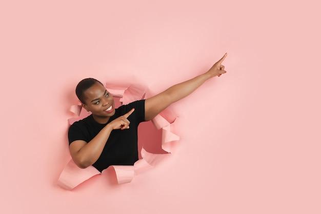 가리키는. 쾌활 한 아프리카 계 미국인 젊은 여성이 찢어진 된 산호 종이, 감정 및 표현에 포즈.