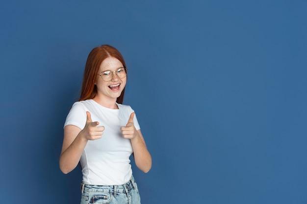 가리키고, 선택합니다. 파란색 벽에 백인 어린 소녀의 초상화입니다. 귀여운 주근깨가 있는 아름다운 여성 redhair 모델입니다. 인간의 감정, 표정의 개념입니다.
