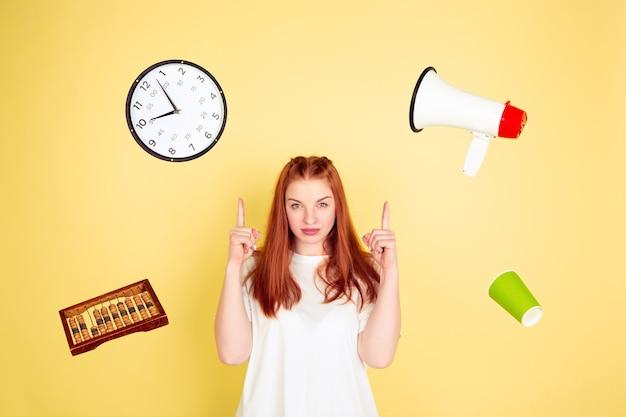 Указывая, выбирая. портрет кавказской молодой женщины на желтом фоне студии, слишком много задач. как правильно распоряжаться временем. концепция работы, бизнеса, финансов, фриланса, самоуправления, планирования.