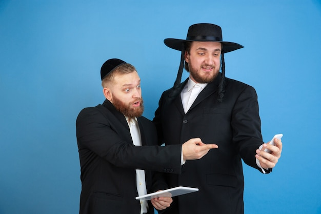 Indicare, scegliere. ritratto di giovani uomini ebrei ortodossi isolati sulla parete blu. purim, affari, festival, vacanza, celebrazione pesach o pasqua ebraica, ebraismo, concetto di religione.