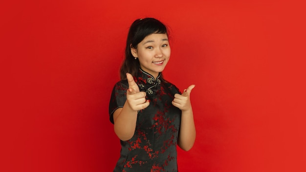 Pointing on, choosing, smiling. happy chinese new year 2020. asian young girl's portrait on red background. female model in traditional clothes looks happy. celebration, human emotions. copyspace.