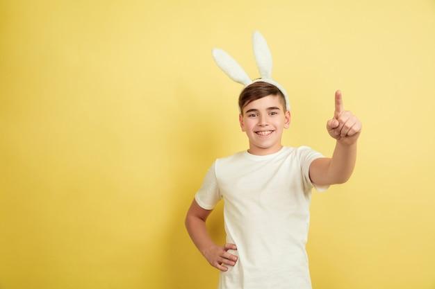 Указывая, выбирая вас. кавказский мальчик как пасхальный кролик на желтом фоне студии. поздравления с пасхой. красивая мужская модель. понятие человеческих эмоций, выражения лица, праздников. copyspace.