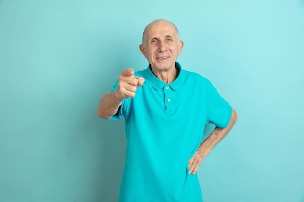 Indicando, scegliendo te. ritratto dell'uomo maggiore caucasico sullo studio blu.