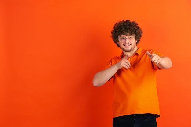 Pointing, choosing you. caucasian young man's monochrome portrait on orange studio