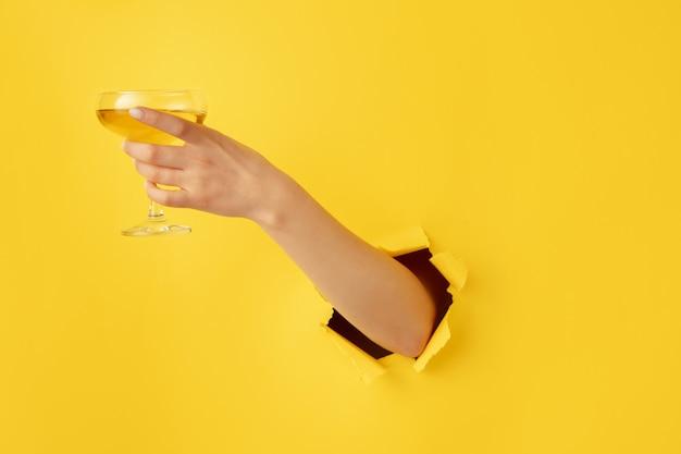 ポインティング。引き裂かれた黄色の紙の穴の背景で身振りで示す女性の手。突破、突破口。ビジネス、金融、ショッピング、提案、販売、広告の概念。