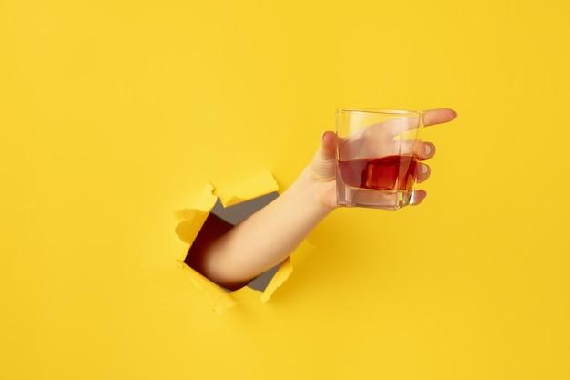 가리키는. 찢어진 된 노란 종이 구멍 배경에서 몸짓 여성 손. 돌파구, 돌파구. 비즈니스, 금융, 쇼핑, 제안, 판매, 광고의 개념.