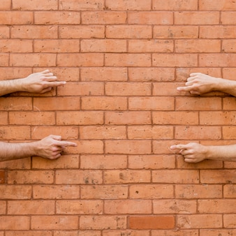 Pointing fingers at each other on brick wall