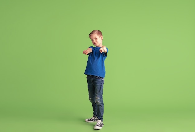 Pointing on. happy boy playing and having fun on green  wall. caucasian kid in bright cloth looks playful, laughting, smiling. concept of education, childhood, emotions, facial expression.