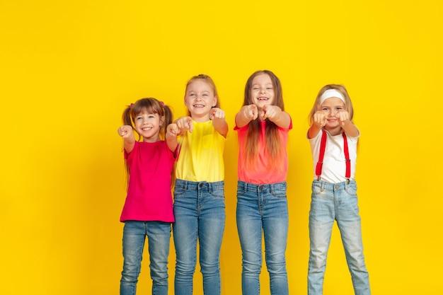 ポインティング。黄色のスタジオの壁で一緒に遊んで楽しんでいる幸せな子供たち。