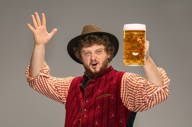 Указывая. счастливый улыбающийся человек, одетый в традиционный австрийский или баварский костюм, жестикулирующий, изолированный на серой студии