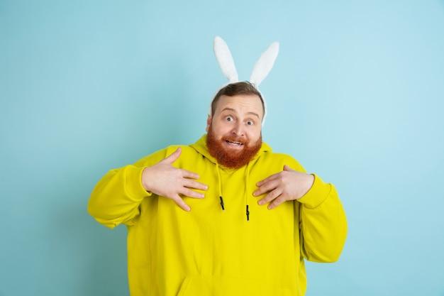 Puntando su se stesso. uomo caucasico come un coniglietto di pasqua con abiti casual luminosi su sfondo blu studio.