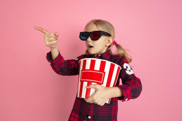 Указывая в 3d очках. портрет кавказской маленькой девочки на розовой стене. красивая женская модель со светлыми волосами. понятие человеческих эмоций, выражения лица, продаж, рекламы, кино, детства.