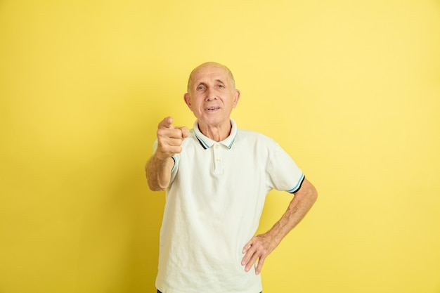 가리키는. 노란색 스튜디오 배경에 고립 된 백인 수석 남자의 초상화. 아름다운 남성 감정 모델. 인간의 감정, 표정, 판매, 웰빙, 광고의 개념. copyspace.