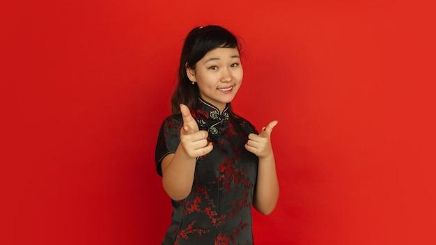 指さし、選び、笑顔。ハッピーチャイニーズニューイヤー2020。赤い背景の上のアジアの若い女の子の肖像画。伝統的な服を着た女性モデルは幸せそうに見えます。お祝い、人間の感情。コピースペース。