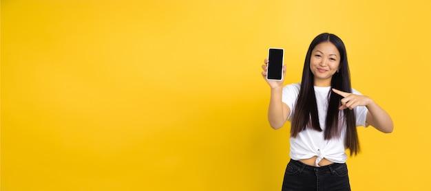 電話を指しています。黄色で隔離の若いアジアの女性の肖像画