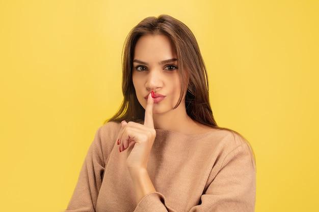 Указывая. портрет молодой кавказской женщины, изолированной на желтом