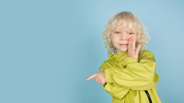 Indicando di nascosto. ritratto di bello ragazzino caucasico isolato sulla parete blu dello studio. modello maschio riccio biondo
