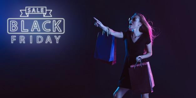 충격을 가리키는. 어두운 스튜디오 backgound에 네온 불빛에 젊은 아름 다운 여자의 초상화. 네온 글자. 인간의 감정, 블랙 프라이데이, 사이버 먼데이, 구매, 판매, 금융 개념. 카피스페이스.