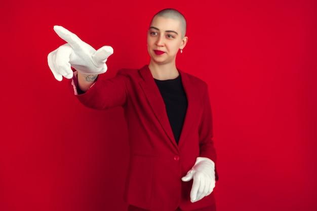 가리키며, 보여주고 있습니다. 빨간 스튜디오 벽에 격리된 젊은 백인 대머리 여성의 초상화.
