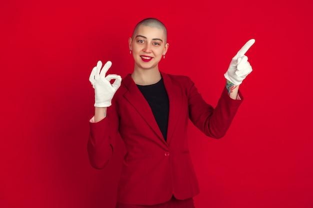 가리키는, 보여주는. 빨간 벽에 고립 된 젊은 백인 대머리 여자의 초상화. 재킷에 아름 다운 여성 모델입니다. 인간의 감정, 표정, 판매, 광고 개념. 이상한 문화.
