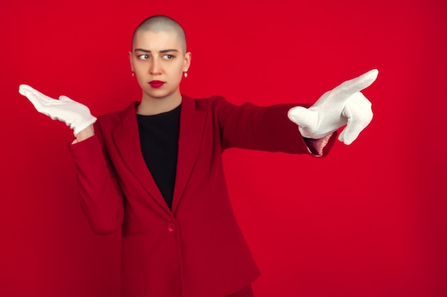 指さす、見せる。赤い壁に分離された若い白人のハゲ女性の肖像画。